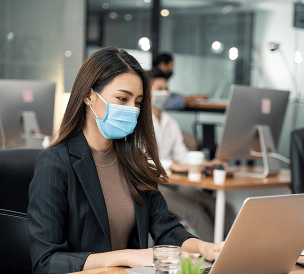 Women working in an office wearing a mask during COVID-19