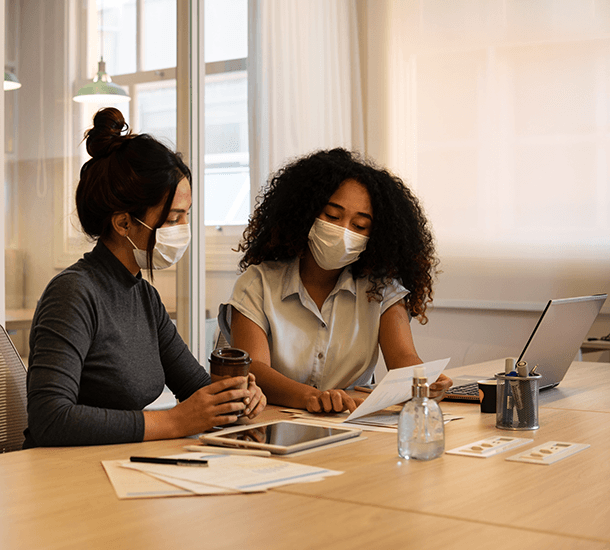 Women working in an office wearing masks due to the new Delta variant